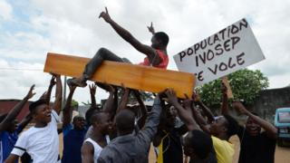 Protestors carry coffins as they wave placards during a rally in front of the morgue of Yopougon University Hospital in Abidjan on March 7, 2018, as they stage a protest against IVOSEP - the dominant funeral service provider in Ivory Coast. Hundreds of small undertaker firms in Ivory Coast have gone on strike over what they described as abusive practices by the country's dominant funeral company.