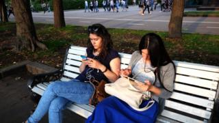 Девушки читают с планшентов в Парке Горького