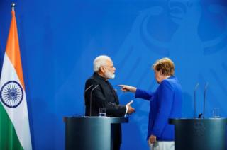 German Chancellor Angela Merkel gestures next to Indian Prime Minister Narendra Modi at the end of their news conference at the Chancellery in Berlin, Germany