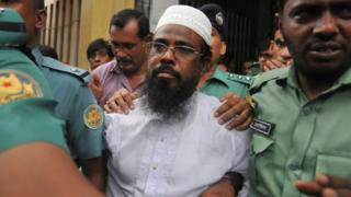 A file photo from 2014 shows Bangladeshi Harkat-ul Jihad al Islami leader Mufti Abdul Hannan flanked by police officers after a court appearance in Dhaka