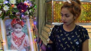 Jiranuch Trirat, mother of 11-month-old daughter who was killed by her father who broadcast the murder on Facebook, stands next to a picture of her daughter at a temple in Phuket.