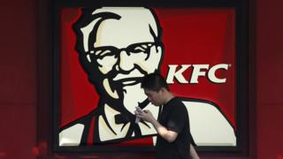 A man walks past a logo of KFC, outside a restaurant in Shanghai, China, July 30, 2015.