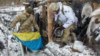 Ukrainian servicemen take Ukrainian National flag from a shelter damaged after shelling, in a front line near Novognatovka, Donetsk area, Ukraine, 07 February 2017.