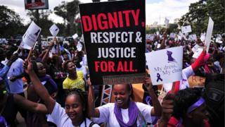 Women hold up placards and shout slogans during a rally against violence to women, on November 17, 2014 in Nairobi.
