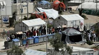 Refugees and migrants line up inside Moria detention center in Mytilene one day before the visit of Pope Francis on April 15, 2016