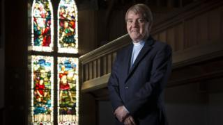 The Reverend Dr Russell Barr, the Church of Scotland's moderator designate standing in front of a stained glass window