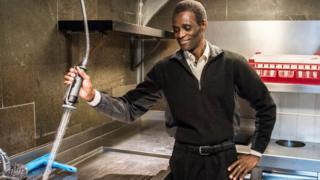 Employee Ali Sonko poses in the kitchen of Noma restaurant in Copenhagen