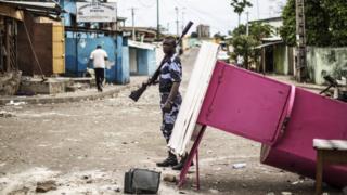 A police officer patrols near a barricade in Libreville in an attempt to secure neighbourhoods from looters, 2 September 2016