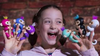 A girl plays with the Fingerlings toy