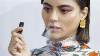 A model smokes before the Snow Xue Gao Spring Summer 2018 Show during New York Fashion Week on September 8, 2017 in New York