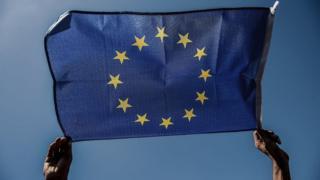 AB bayrağı taşıyan bir göçmen