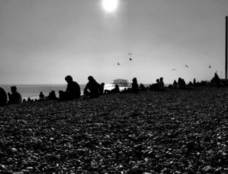 Black and white photograph of a people sat on a pebble beach