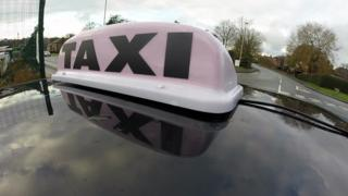General view of a TAXI sign on the roof of a licensed mini cab
