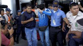 One of the Syrians is escorted by police at Tegucigalpa airport