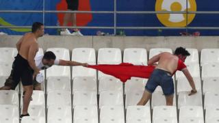 A fan has the shirt ripped from his back inside the Stade Velodrome