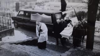 A police photo of the funeral shows a priest at Mollendal cemetery, while six police officers carry a white coffin containing the body of the Isdal Woman