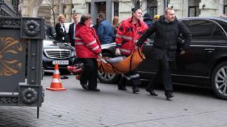 Предполагаемого убийцу несут к скорой помощи
