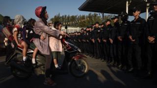 Bir kadın çocuklarıyla motosiklet üzerinde, polisler geçmesine izin vermiyor.