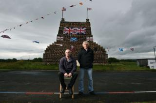 Stewart McClelland (L) and Winston Wylie (R) proudly display their finished bonfire on the Ballykeel 2 estate on July 10, 2017 in Ballymena, Northern Ireland. The