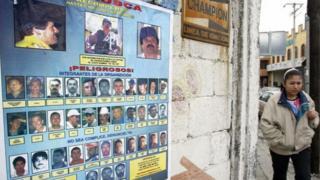 Mulher passa ao lado de cartaz de traficantes procurados