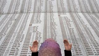 In this 2008 picture, a Bosnian Muslim woman prays at the memorial wall with the names of the victims of the Srebrenica massacre