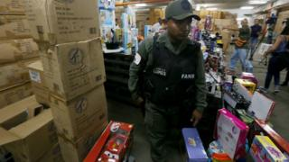 A handout photo released by Venezuelan News Agency (AVN) shows a member of Venezuelan Armed Forces walking among boxes of toys during an operation at a toy store in Caracas, Venezuela, 09 December 2016.