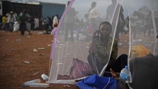 A woman uses her phone inside a tent as she sits inside a make-shift camp at Nimule border, in Amuru Distric in Uganda - Saturday 16 July 2016