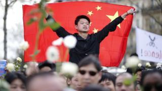 巴黎共和國廣場悼念劉少堯集會現場的一名年輕華裔男子把中國國旗披在身上(2/4/2017)