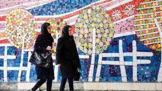 Iranian women walk past mural in Tehran (file photo)
