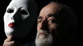 Bearded man holding mask