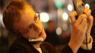 شخص يلتقط صورا بالكاميرا خلال التحدث في هاتفه المحمول