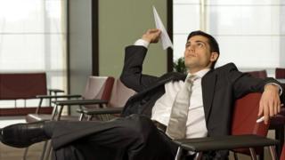 Homem brinca com avião de papel