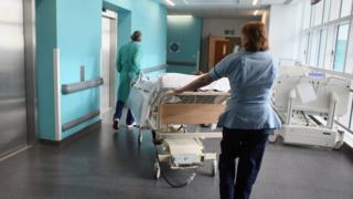 A bed-ridden patient being moved in a hospital corridor
