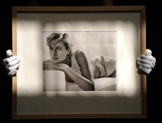 An employee holds a framed photograph of Diana, to be auctioned at Christie's