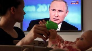 """A Russian woman plays with her baby while watching the annual Question and Answer nationwide live-broadcast television and radio shows """"Direct Line with Vladimir Putin"""" at their home in Moscow, Russia"""