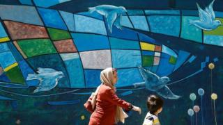 woman and child walk past mural with birds in Iran