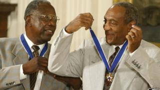 Actor Comedian Bill Cosby (right) jokes with baseball great Hank Aaron after they both received the Presidential Medal of Freedom Award from U.S. President George W. Bush during a ceremony 9 July 2002