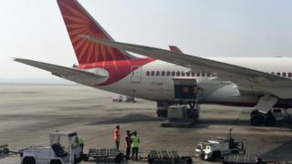 Airport workers load an Air India jet at the main terminal of the Indira Gandhi International airport in New Delhi on November 25, 2014.