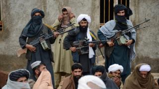 Afghan Taliban fighters listen to Mullah Mohammed Rasool, unseen, the newly-elected leader of a breakaway faction of the Taliban