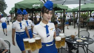 August 12, 2016 - a waitress carrying jugs of beer to guests before the opening of the Pyongyang Taedonggang Beer Festival on the banks of the Taedong river in Pyongyang