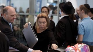 A woman putting a bag in a tray for screening at an airport