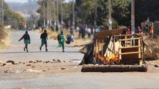 Schoolchildren run past a burning barricade, following a job boycott called via social media platforms, in Harare, Wednesday, July,6, 2016