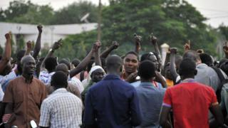 People gather at the Place de la Nation in Ouagadougou on 16 September 2015, a few hours after Burkina Faso's interim president and prime minister were detained at the presidential palace by guards loyal to ousted leader Blaise Compaore