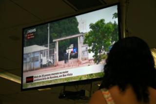 Mujer ve la noticia de la masacre en la prisión de Boa Vista, en Roraima, Brasil, por televisión.