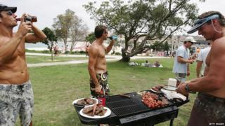 Men standing around a barbecue in Australia