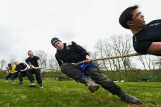 A group of men strain at a tug of war rope.