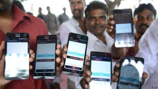 Indian drivers for Uber show mobiles phones given to them by the company