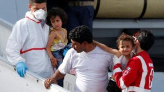 Migrants disembark from a Italian navy ships in Porto Empedocle, 26 May 26