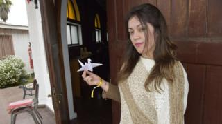 Estefanía holds up a paper dove she has made as decoration for the Pope's visit