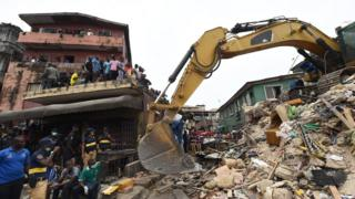 Bulldozer dey find dead bodi of di people wey one four-storey building collapse on top for Lagos in July 2017.
